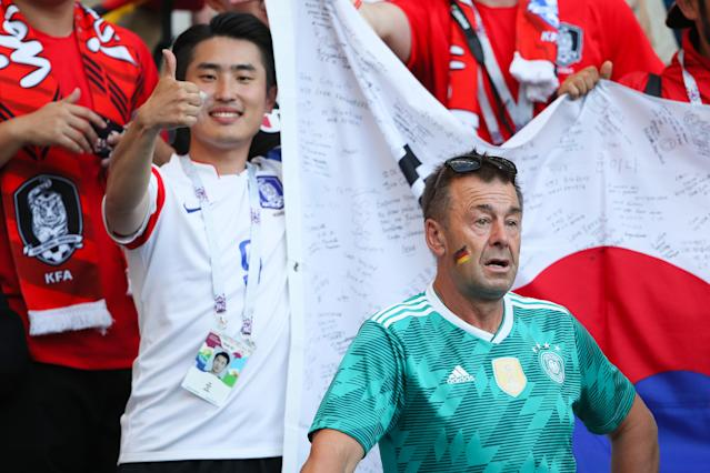 <p>A Germany fan looks dejected as a Korea fan gives a thumbs up at the end of the 2018 FIFA World Cup Russia group F match between Korea Republic and Germany at Kazan Arena on June 27, 2018 in Kazan, Russia. (Photo by Matthew Ashton – AMA/Getty Images) </p>