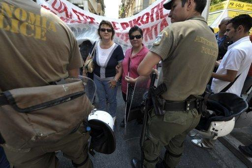 Blind protesters face police during a demonstration of disabled people protesting against cuts in Greece