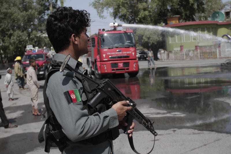 An Afghan policeman stands guard near the site of an explosion in front of Governor House in Jalalabad east of Kabul, Afghanistan, Sunday, Sept. 1, 2013. A bomb attached to a vehicle of the Jalalabad mayor exploded on Sunday, apparently targeting the mayor of the eastern city of Jalalabad, but wounded his driver instead. (AP Photo/Rahmat Gul)
