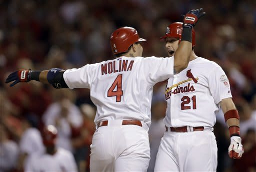 St. Louis Cardinals' Yadier Molina (4) is congratulated by teammate Allen Craig after hitting a two-run home run during the second inning of a baseball game against the Washington Nationals on Friday, Sept. 28, 2012, in St. Louis. (AP Photo/Jeff Roberson)