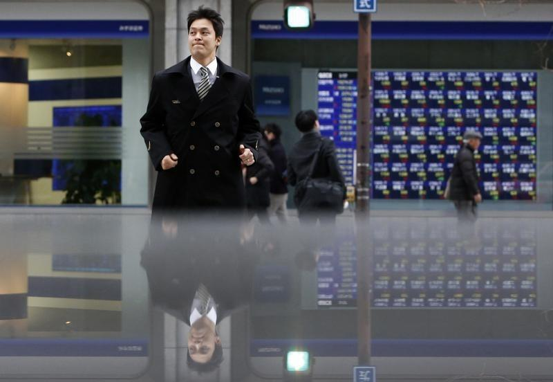 Pedestrians pass by an electronic board displaying stock prices, which are reflected in a polished stone surface, in Tokyo