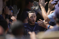 Tampa Bay Rays' Brandon Lowe, right, high-fives teammates as he reaches the dugout after hitting a two-run home run against the Oakland Athletics during the sixth inning of a baseball game Saturday, May 8, 2021, in Oakland, Calif. (AP Photo/Tony Avelar)