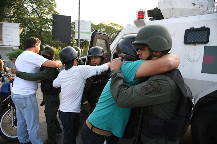 Supoprters of self-proclaimed acting president Juan Guaido hug members of the security forces in Caracas on April 30, 2019. - Venezuelan opposition leader and self-proclaimed acting president  Juan Guaido said on Tuesday that troops had joined his campaign to oust President Nicolas Maduro as the government vowed to put down what it said was an attempted coup. (Photo: Yuri Cortez/AFP/Getty Images)