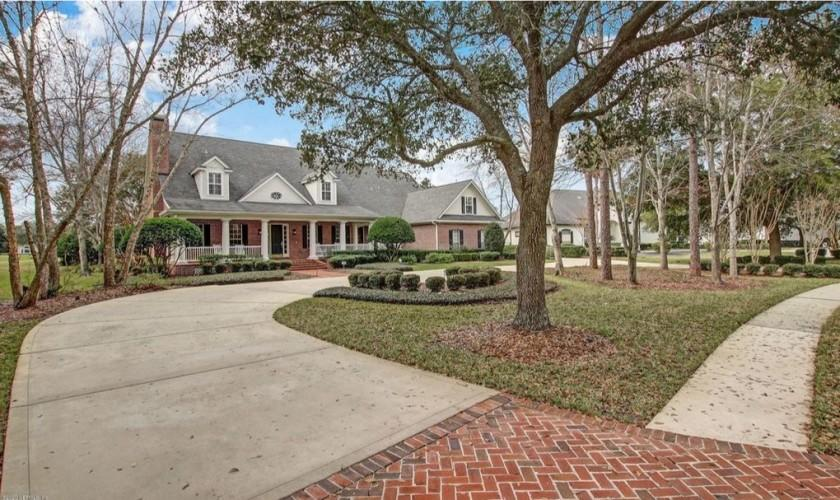 The brick-clad two-story features a motor court in front and a dining gazebo out back that descends to a pond.