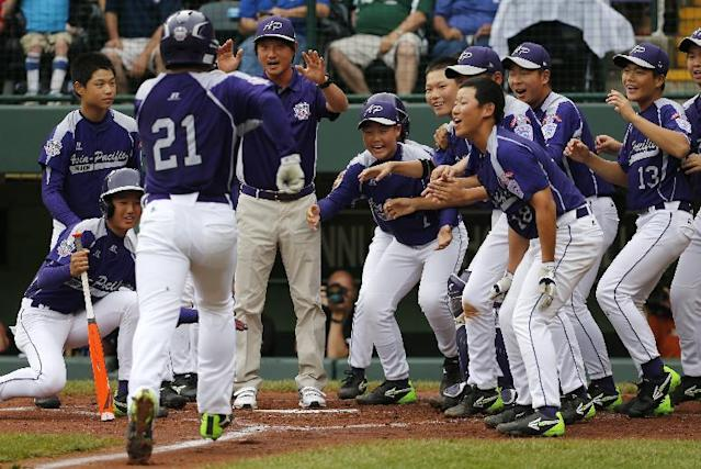 Seoul's Hae Chan Choi (21) is greeted by teammates after hitting a two-run home run off Tokyo pitcher Takuma Takahashi in the second inning of a International semi-final baseball game against Tokyo at the Little League World Series tournament in South Williamsport, Pa., Wednesday, Aug. 21, 2013. (AP Photo/Gene J. Puskar)