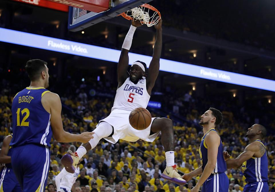 Los Angeles Clippers' Montrezl Harrell (5) scores as Golden State Warriors' Andrew Bogut (12), Klay Thompson, second from right, and Andre Iguodala watch during the second half in Game 5 of a first-round NBA basketball playoff series, Wednesday, April 24, 2019, in Oakland, Calif. (AP Photo/Ben Margot)