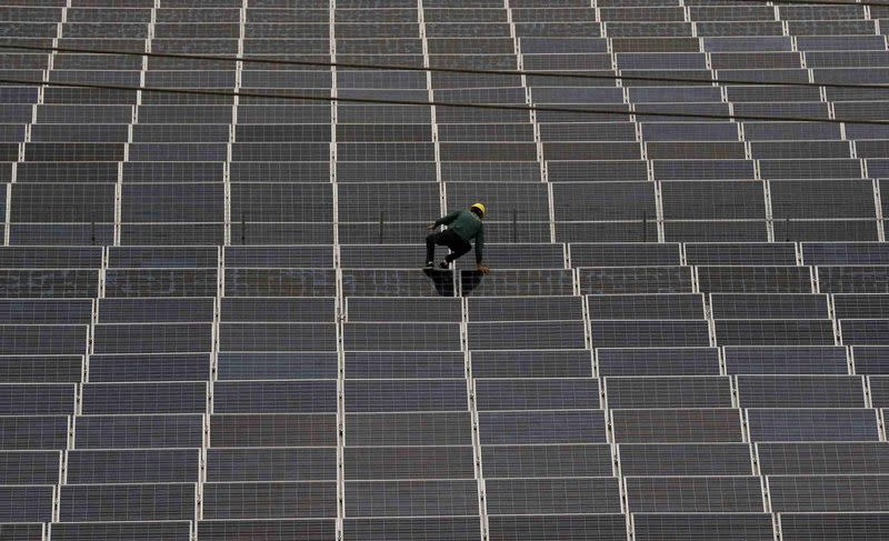 A worker climbs over a solar panel at a solar factory in Longyou county