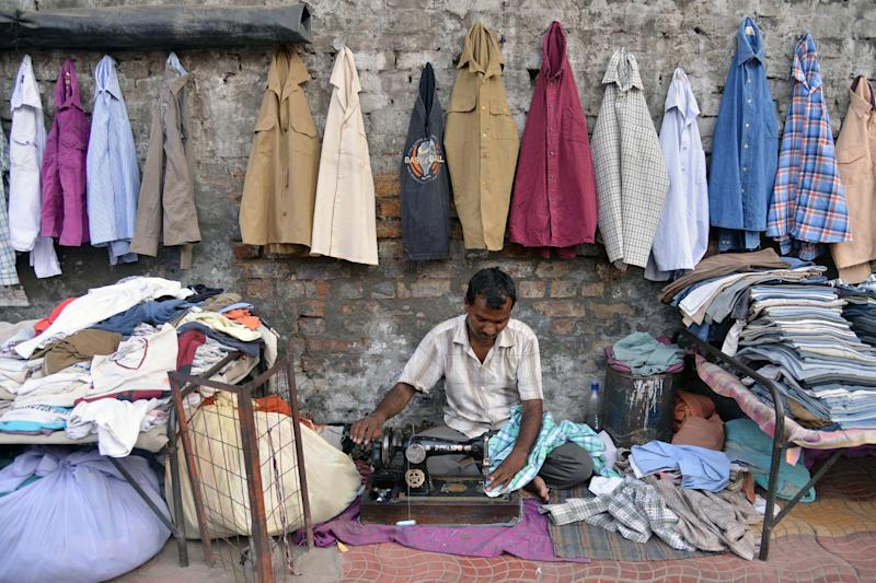 An Indian tailor repairs used clothes at a roadside in Amritsar, August 22, 2014 (AFP Photo/Narinder Nanu)