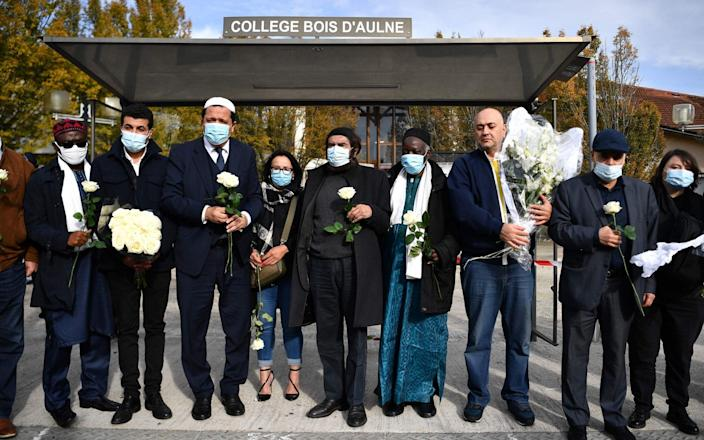 Imam of Drancy Hassen Chalghoumi (3rd L) and French Jewish writer Marek Halter (C) attend a gathering of imams outside the Bois d'Aulne secondary school - AFP