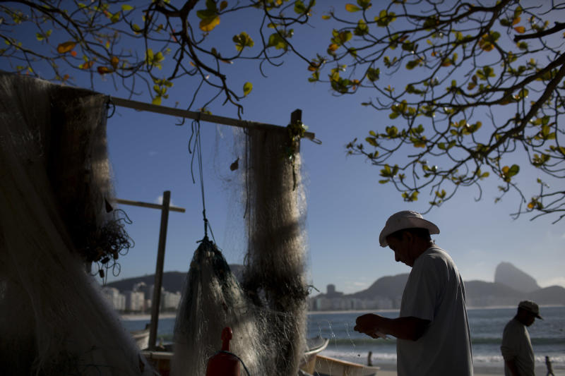 In this Aug. 21, 2013 photo, a fisherman fixes his fishing net on Copacabana beach in Rio de Janeiro, Brazil. This isn't your average fishermen's port. It's Rio de Janeiro's famed Copacabana beach, its sands forming a golden crescent at the edge of a densely populated neighborhood. (AP Photo/Felipe Dana)