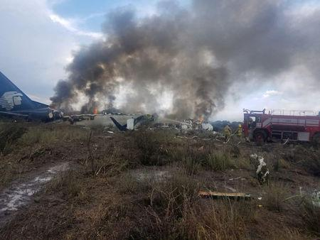 Firefighters douse a fire as smoke billows above the site where an Aeromexico-operated Embraer passenger jet crashed in Mexico's northern state of Durango, July 31, 2018, in this picture obtained from social media. Proteccion Civil Durango/via REUTERS