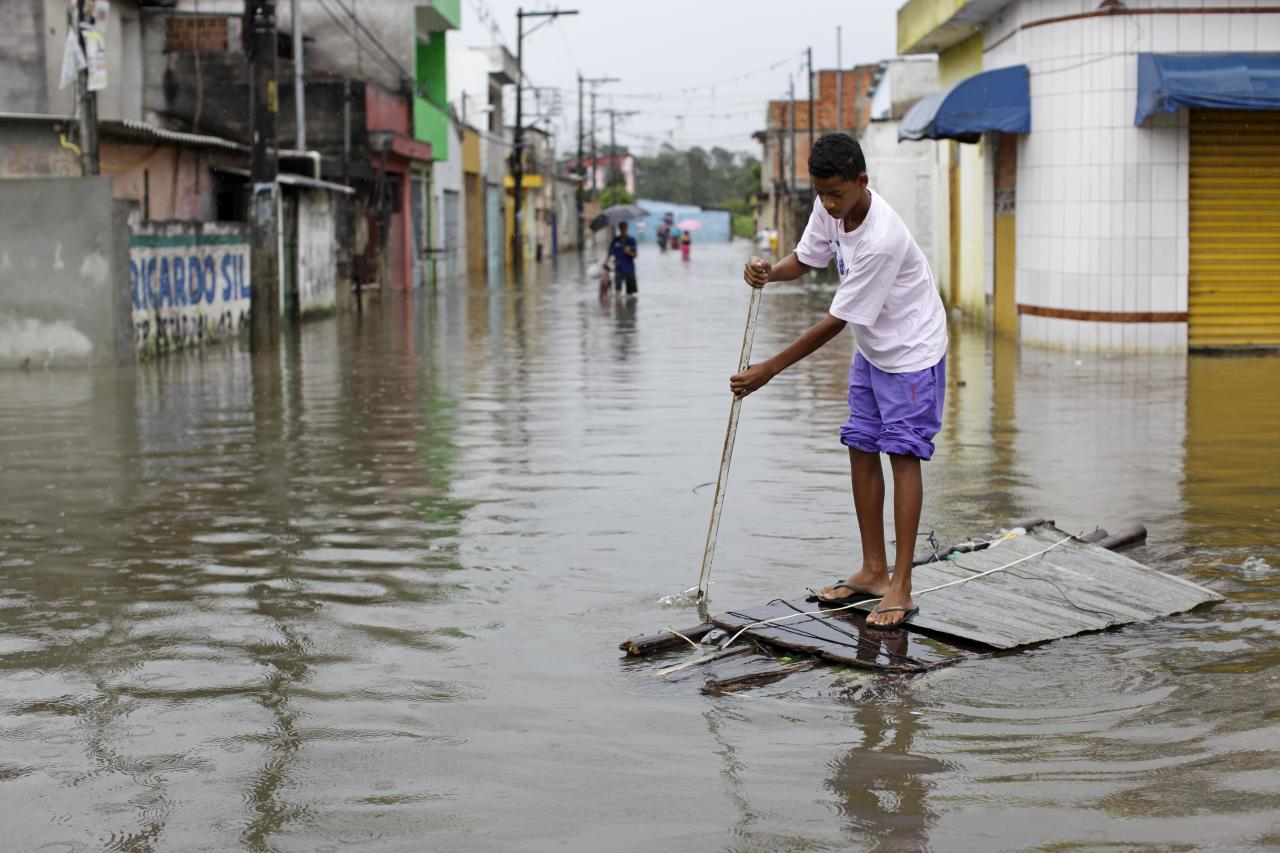 FILE - In this Jan. 13, 2011 file photo, a youth uses a makeshift raft to cross a flooded street in the Vila Itaim neighborhood of Sao Paulo, Brazil. From Chile to Colombia to Mexico, Latin America has been battered recently by wildfires, floods and droughts. While leading climate scientists are unable to pin any single flood or heat wave solely on climate change, experts say the number of extreme weather events is increasing worldwide and the evidence suggests global warming is having an impact. (AP Photo/Nelson Antoine, File)