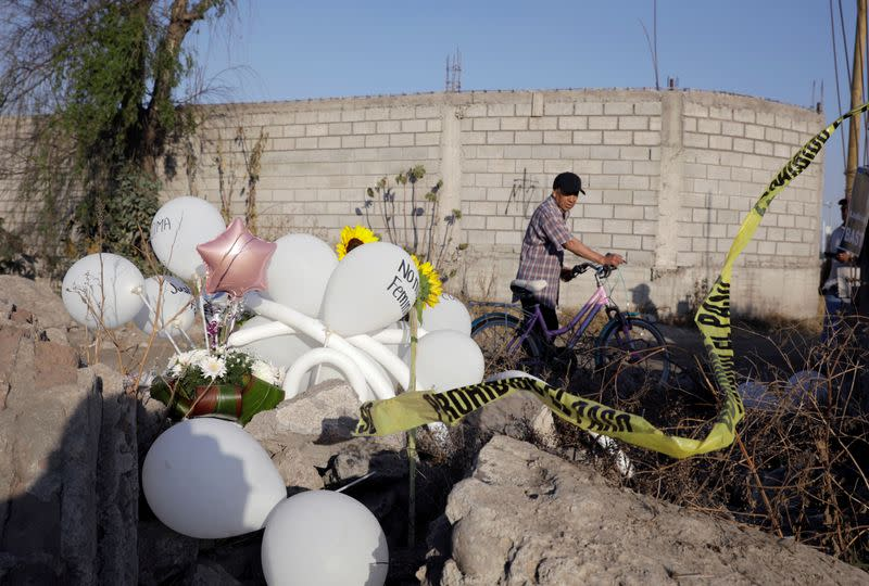 A man looks on next to white balloons and flowers at the site where the body of seven-year old Fatima Cecilia Aldrighett was discovered in Mexico City