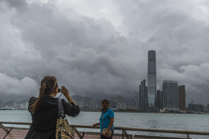 Tourists take pictures in front of the Kowloon skyline during a thunderstorm in Hong Kong caused by Typhoon Kalmaegi on September 16, 2014 (AFP Photo/Xaume Olleros)