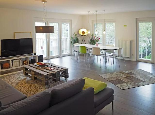 <p>The living/dining room is large and lets in a lot of natural light. (Airbnb) </p>