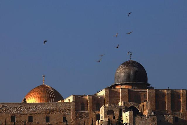 <b>JERUSALEM, ISRAEL:</b> Birds fly over al-Aqsa mosque and the golden Dome of the Rock Islamic shrine as seen from the East Jerusalem neighborhood of Silwan.