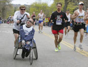FILE - In this April 17, 2006, file photo, Dick Hoyt pushes his son Rick through Newton, Mass., during their 25th Boston Marathon together. Dick Hoyt, who last competed with his son in the Boston Marathon in 2014, has died, the Boston Athletic Association announced Wednesday, March 17, 2021. He was 80. (AP Photo/Adam Hunger, File)