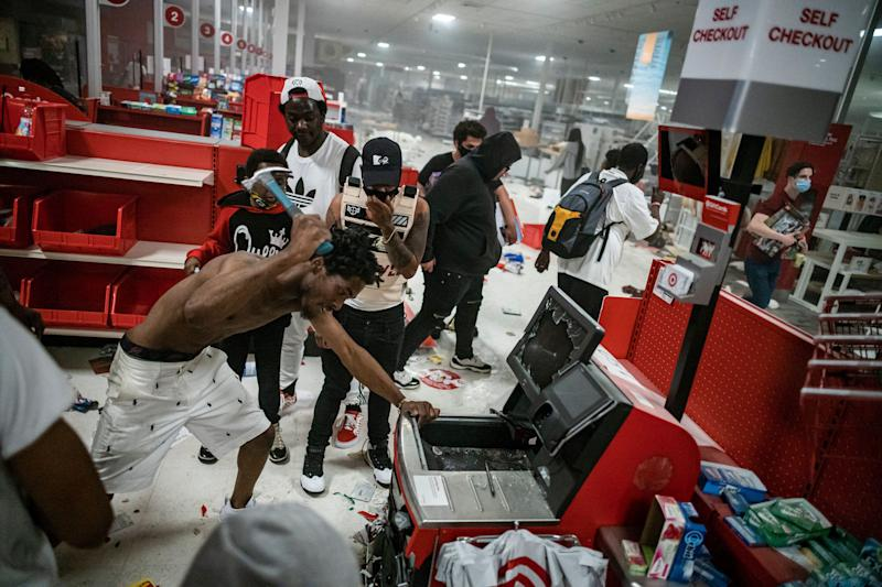 <strong>A looter uses a claw hammer as he tries to break in to a cash register at a Target store in Minneapolis.</strong> (Photo: ASSOCIATED PRESS)