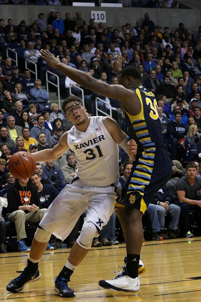 Xavier's Isaiah Philmore drives to the basket past Marquette's Deonte Burton in the first half of their NCAA college basketball game at Xavier in Cincinnati, Thursday, Jan. 9, 2014. (AP Photo/Tom Uhlman)
