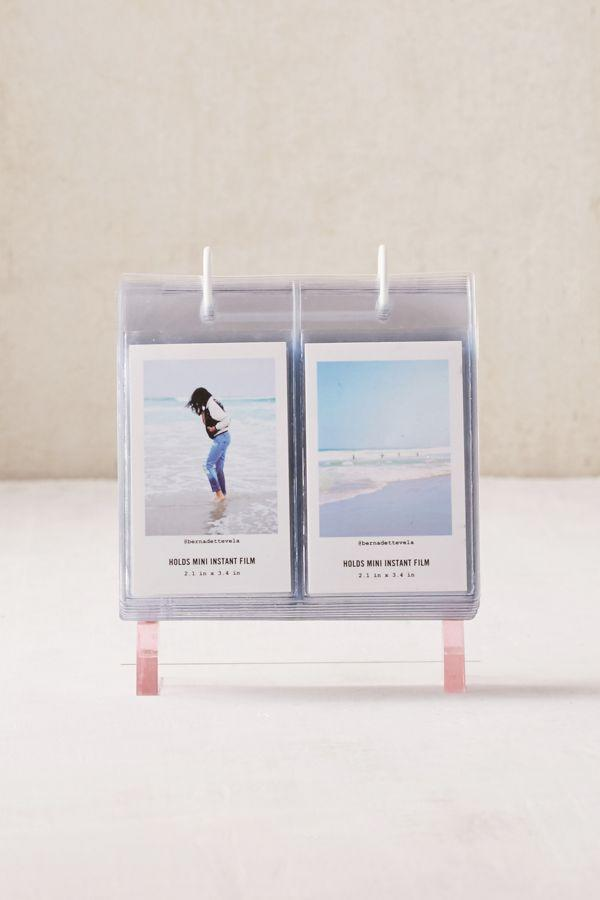 """<h3><a href=""""https://www.urbanoutfitters.com/shop/mini-instax-acrylic-album-photo-frame"""" rel=""""nofollow noopener"""" target=""""_blank"""" data-ylk=""""slk:Urban Outfitters Mini Instax Photo Frame"""" class=""""link rapid-noclick-resp"""">Urban Outfitters Mini Instax Photo Frame</a></h3><br>A clever and stylish way for giftees to display all of their Mini Instax prints. <br><br><strong>Urban Outfitters</strong> Mini Instax Acrylic Album Photo Frame, $, available at <a href=""""https://www.urbanoutfitters.com/shop/mini-instax-acrylic-album-photo-frame"""" rel=""""nofollow noopener"""" target=""""_blank"""" data-ylk=""""slk:Urban Outfitters"""" class=""""link rapid-noclick-resp"""">Urban Outfitters</a>"""