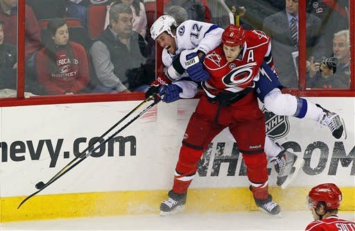 Carolina Hurricanes' Tim Gleason (6) checks Tampa Bay Lightning's Ryan Malone (12) into the boards during the third period of an NHL hockey game in Raleigh, N.C., Saturday, March 3, 2012. Tampa Bay won 4-3 in overtime. (AP Photo/Karl B DeBlaker)