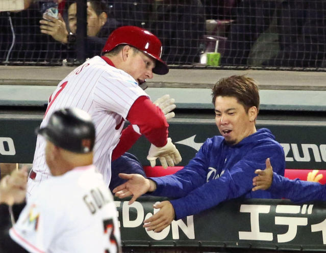MLB All-Star designated hitter Rhys Hoskins of the Philadelphia Phillies celebrates with starter Kenta Maeda, right, of the Los Angeles Dodgers at bench after hitting a solo home-run off All Japan starter Daichi Osera in the second inning of Game 4 at their All-Stars Series baseball at Mazda Zoom-Zoom Stadium in Hiroshima, western Japan, Tuesday, Nov. 13, 2018. (Kyodo News via AP)