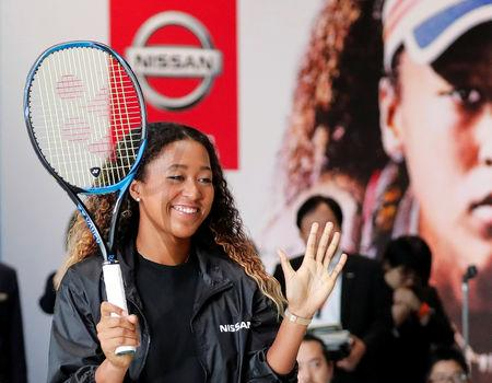 U.S. Open tennis champion Naomi Osaka reacts as she hits a ball to Nissan Motor's Senior Vice President Asako Hoshino after a contract signing ceremony at Nissan's global headquarters in Yokohama, Japan, September 13, 2018.   REUTERS/Toru Hanai