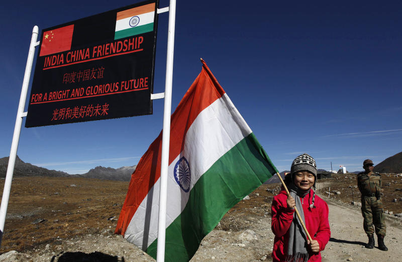 FILE - In this Oct. 21, 2012 file photo, an Indian girl poses for photographs with an Indian flag at the Indo China border in Bumla at an altitude of 15,700 feet (4,700 meters) above sea level in Arunachal Pradesh, India. While the recent troop standoff in a remote Himalayan desert spotlights a long-running border dispute between China and India, the two emerging giants are engaged in a rivalry for global influence that spreads much farther afield. (AP Photo/Anupam Nath, File)