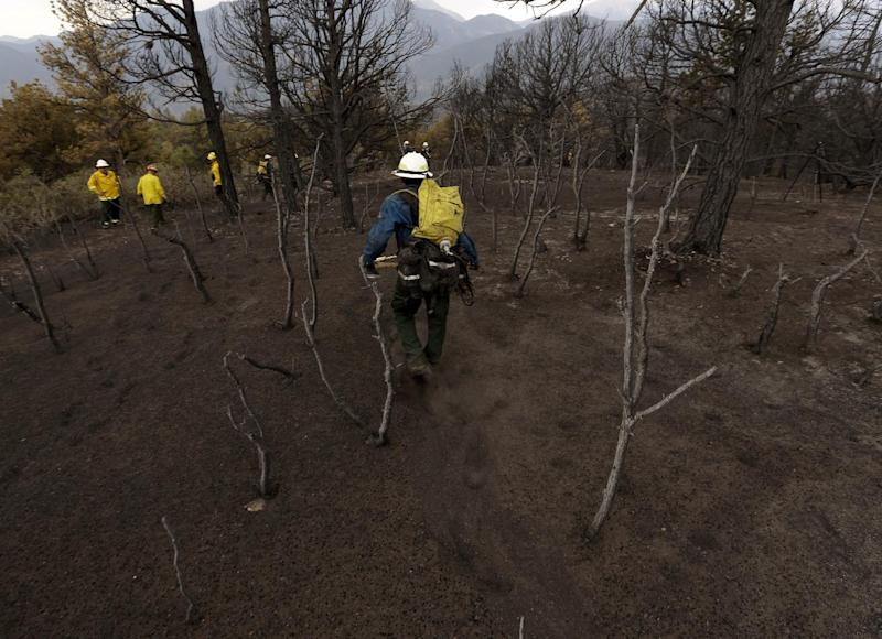 """Members of Bighorn 209, a hand crew from the Crow Agency in Montana check for hot spots from the Waldo Canyon Fire west of Colorado Springs, Colo., Friday, June 29, 2012. After declaring a """"major disaster"""" in the state early Friday and promising federal aid, President Barack Obama got a firsthand view of the wildfires and their toll on residential communities. More than 30,000 people have been evacuated in what is now the most destructive wildfire in state history. (AP Photo/Chris Carlson)"""