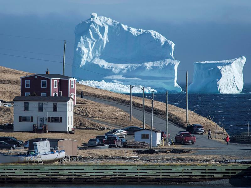 A massive iceberg traveling south is photobombing a small Canadian fishing village