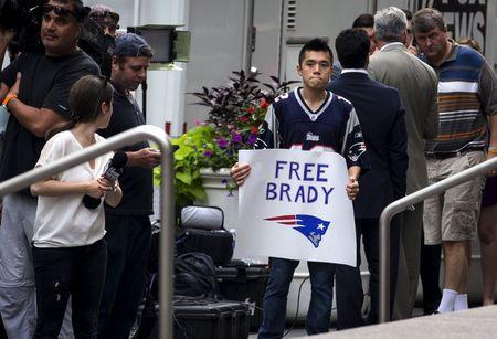 Supporter of New England Patriots quarterback Brady holds a sign as he stands with a large crowd of media outside the NFL headquarters offices in the Manhattan borough of New York
