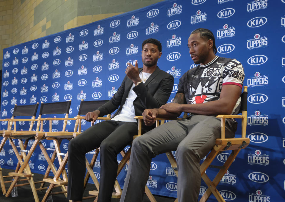 Paul George, left, and Kawhi Leonard attend a press conference in Los Angeles, Wednesday, July 24, 2019. Nearly three weeks after the native Southern California superstars shook up the NBA by teaming up with the Los Angeles Clippers, the dynamic duo makes its first public appearance. (AP Photo/Ringo H.W. Chiu)