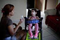 Rosana Vieira Alves, 28, feeds her two-year-old daughter Luana Vieira, who was born with microcephaly, at their house in Olinda, Brazil, August 9, 2018. REUTERS/Ueslei Marcelino/Files