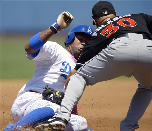 Los Angeles Dodgers' Carl Crawford, left, is tagged out at third by Miami Marlins third baseman Placido Polanco as he tried to tag up on pop out by Matt Kemp during the first inning of the Natioinal League MLB baseball game Sunday, May 12, 2013, in Los Angeles. (AP Photo/Mark J. Terrill)