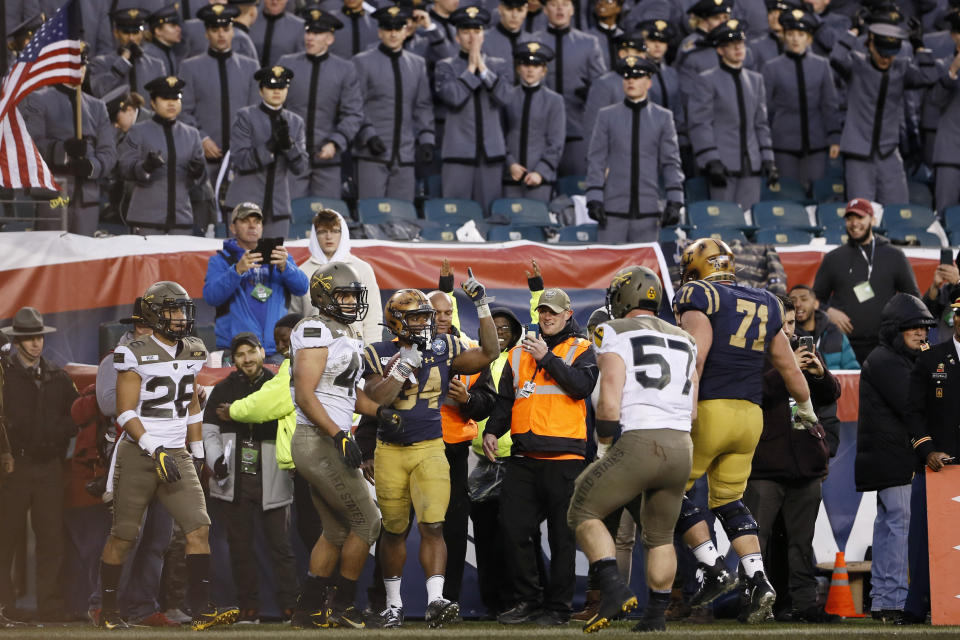 Navy's Jamale Carothers (34) celebrates after scoring a touchdown as Army's Jacob Covington (57), Jeremiah Lowery (43) and Ryan Velez (26) look on during the first half of an NCAA college football game, Saturday, Dec. 14, 2019, in Philadelphia. (AP Photo/Matt Slocum)