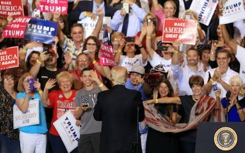 Trump looks to his VIP section during his campaign rally speech in Phoenix - Credit: EPA