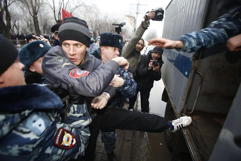 Police officers detain people who gathered for an unsanctioned event in downtown Volgograd, Russia, Monday, Dec. 30, 2013. A bomb blast tore through a trolleybus in the city of Volgograd on Monday morning, killing at least 10 people a day after a suicide bombing that killed at least 17 at the city's main railway station. Volgograd is about 650 kilometers (400 miles) northeast of Sochi, where the Olympics are to be held. (AP Photo/Denis Tyrin)