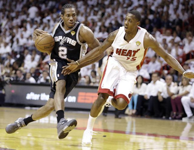 The San Antonio Spurs' Kawhi Leonard (2) moves the ball against Miami Heat's Mario Chalmers (15) during the first half in Game 7 of the NBA basketball championships, Thursday, June 20, 2013, in Miami. (AP Photo/Lynne Sladky)