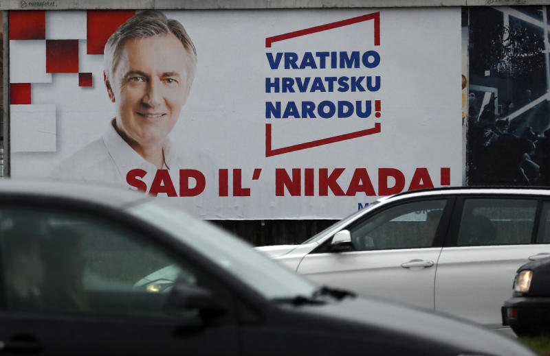 Cars drive past a poster of presidential candidate Miroslav Skoro in Zagreb, Croatia, Saturday, Dec. 21, 2019. Croatia is holding a tight presidential election this weekend that is seen as a test for the conservative government only days before the European Union's newest member state takes over the bloc's presidency for the first time. Poster text reads: ''Let's bring Croatia back to the people!'' and ''Now or never!'' (AP Photo/Darko Vojinovic)