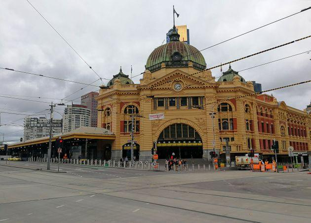 Mobile photo shows few people standing in front of the Flinders Street Station in Melbourne, Australia, March 25, 2020.