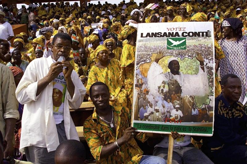 Supporters and members of the Party of Unity and Progress hold an electoral poster of president and presidential candidate general Lansana Conte December 18, 2003 (AFP Photo/Seyllou Diallo)