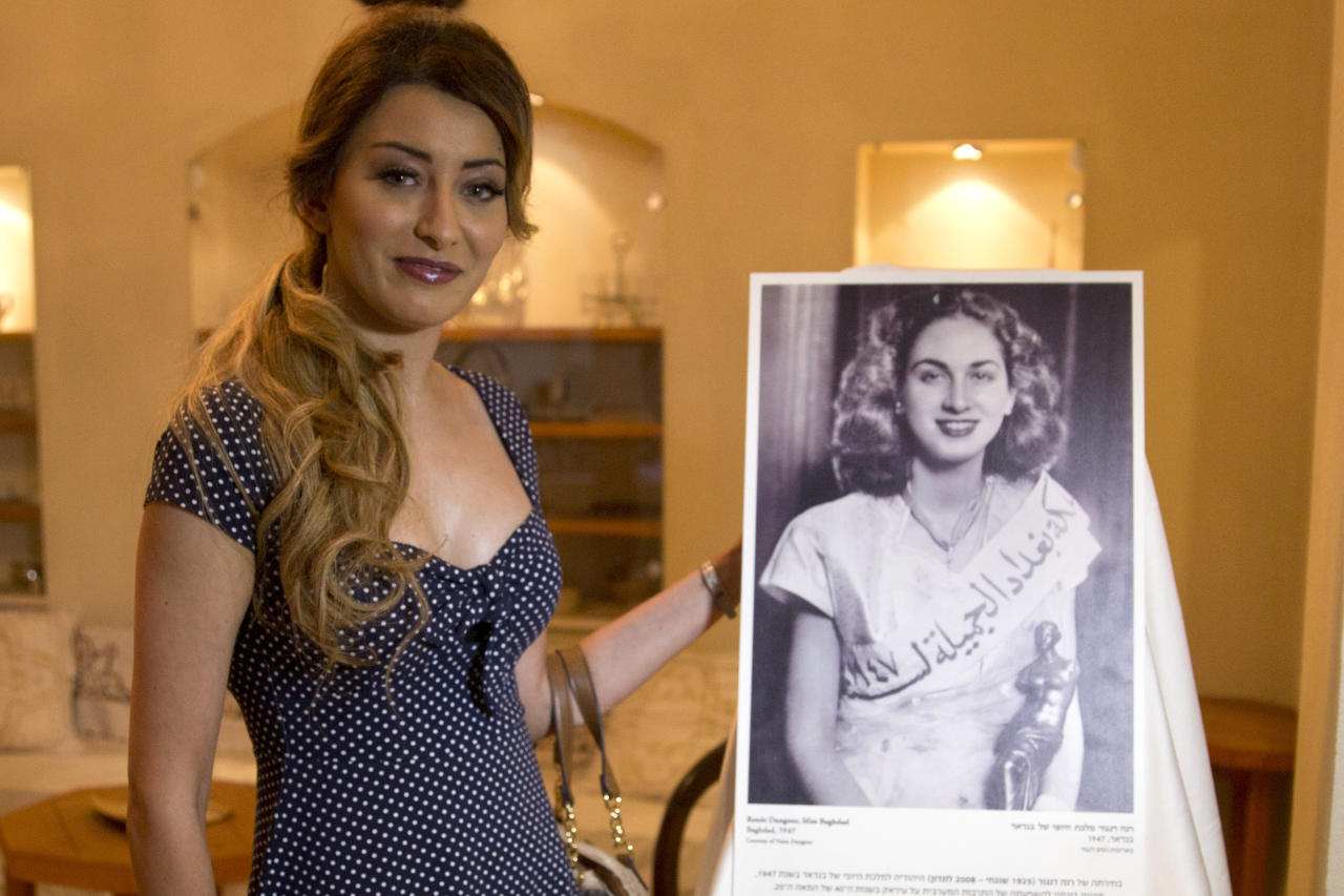 Sarah Idan, Iraq's 2017 Miss Universe beauty pageant contestant, poses with an exhibit showing 1947 Miss Baghdad Renee Dangoor, during a visit to the Babylonian Jewry Heritage Center in Or Yehuda, Israel, Thursday, June 14, 2018. Idan is visiting Israel this week, a trip that has enraged people back home. (AP Photo/Sebastian Scheiner)