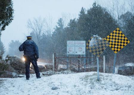 A Royal Canadian Mounted Police (RCMP) officer waits as a group that claimed to be from Syria arrives at the U.S.-Canada border in Hemmingford