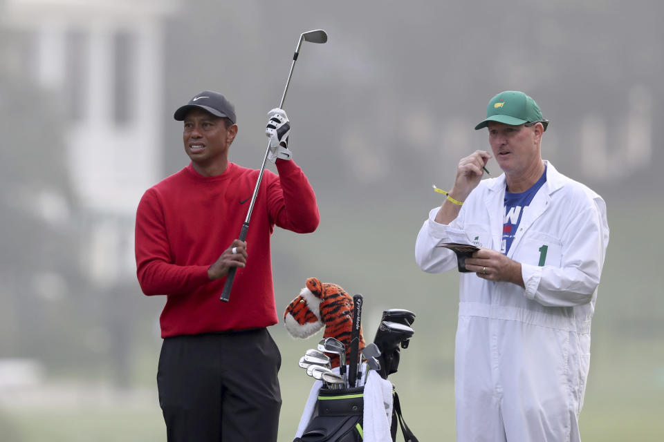 Tiger Woods prepares to hits his second shot on the first fairway with caddie Joe LaCava looking on during the final round of the Masters golf tournament Sunday, Nov. 15, 2020, in Augusta, Ga. (Curtis Compton/Atlanta Journal-Constitution via AP)