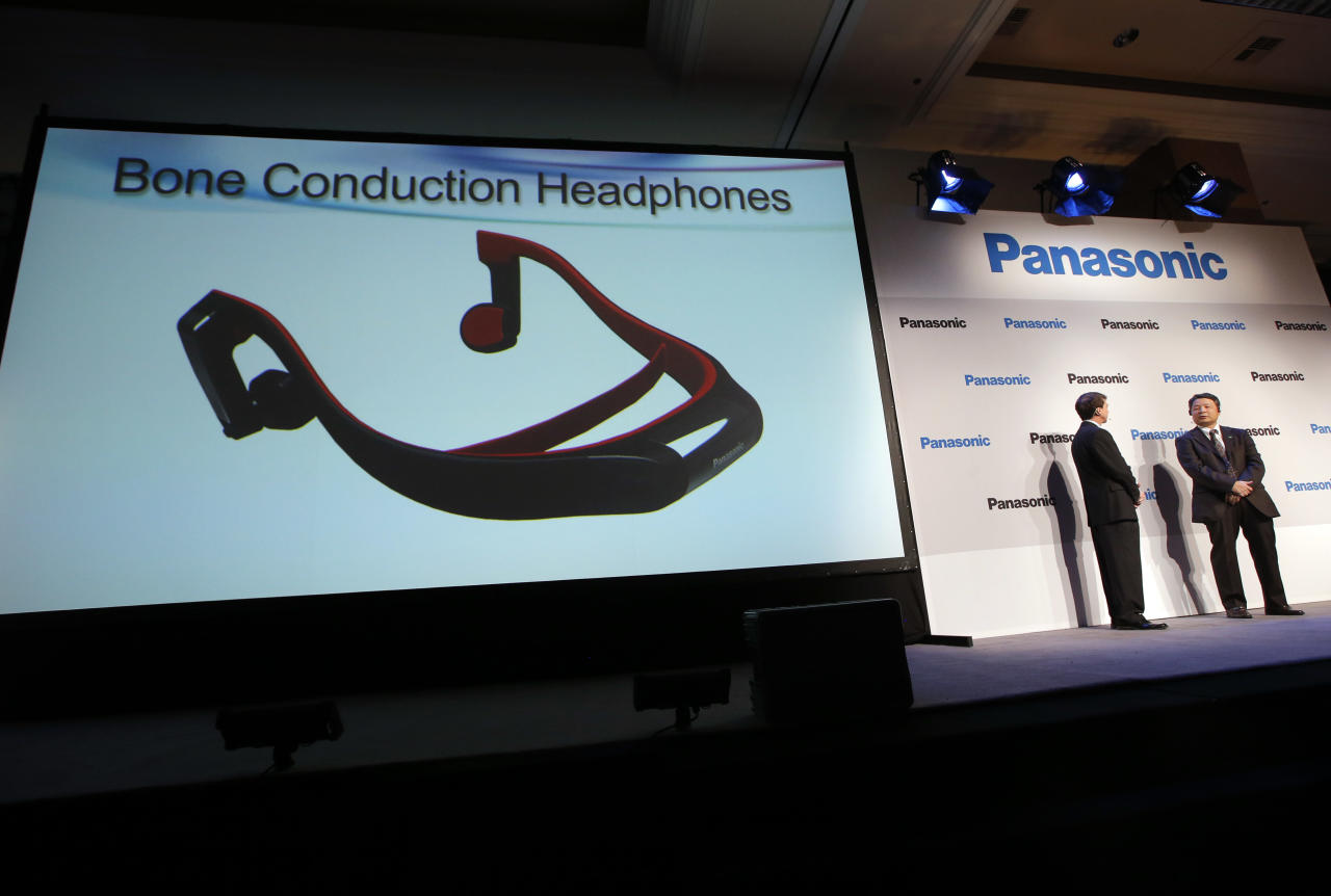 Panasonic's Shiro Kitajima, far right, and Vic Carlson, introduces the bone construction headphones during a news conference at the International Consumer Electronics Show in Las Vegas, Monday, Jan. 7, 2013. The headphones connect to a TV via the Bluetooth wireless standard and attach to your head like a normal set of headphones. But instead of using your ears, the headphones work like hearing aids by transmitting sound waves through your skull. (AP Photo/Jae C. Hong)