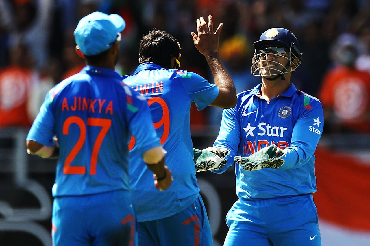 AUCKLAND, NEW ZEALAND - JANUARY 25: MS Dhoni of India celebrates with teammate Ravichandran Ashwin after dismissing Corey Anderson of New Zealand during the One Day International match between New Zealand and India at Eden Park on January 25, 2014 in Auckland, New Zealand.  (Photo by Anthony Au-Yeung/Getty Images)