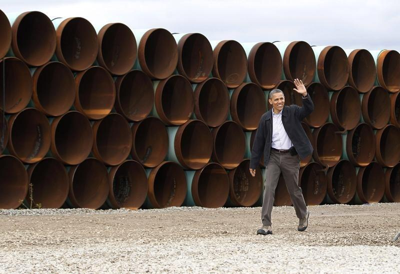 U.S. President Obama walks past oil pipes before delivering remarks on energy independence at Stillwater Pipe Yard in Cushing