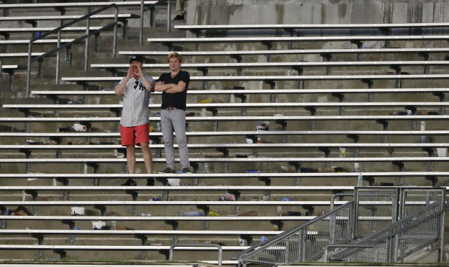 FILE - In this Aug. 2, 2017, file photo, baseball fans cheer from the right field bleacher seats after a rain delay in a baseball game between the New York Yankees and the Detroit Tigers in New York. The crippling grip the coronavirus pandemic has had on the sports world has forced universities, leagues and franchises to evaluate how they might someday welcome back fans. (AP Photo/Julie Jacobson, File)