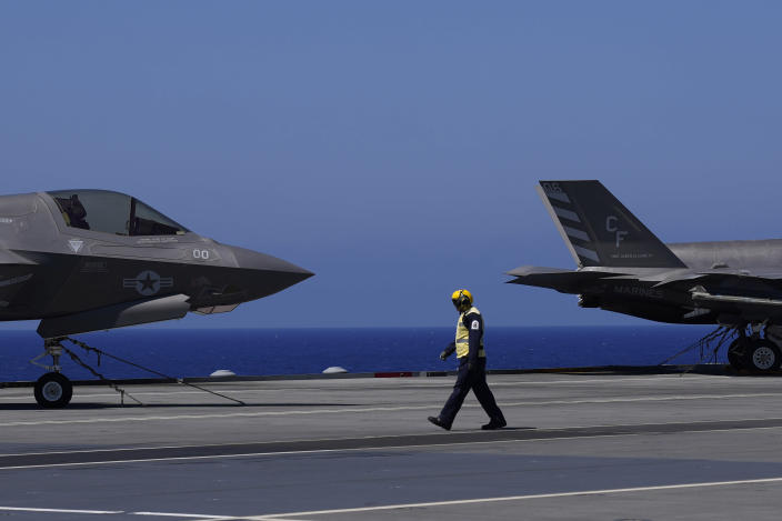 """A crew member walks by the F-35 aircrafts for on the U.K.'s aircraft carrier HMS Queen Elizabeth in the Mediterranean Sea on Sunday, June 20, 2021. The British Royal Navy commanders say the U.K.'s newest aircraft carrier HMS Queen Elizabeth is helping to take on the """"lion's share"""" of operations against the Islamic State group in Iraq as Russian warplanes get an up-close look at the cutting-edge F-35 jet in a """"cat-and-mouse"""" game with British and U.S. pilots. (AP Photo/Petros Karadjias)"""
