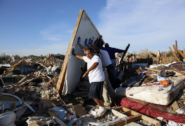 Men lift a wall in an effort to salvage belongings from their tornado-ravaged homes in Moore, Oklahoma May 21, 2013. Rescuers went building to building in search of victims and thousands of survivors were homeless on Tuesday after a massive tornado tore through the Oklahoma City suburb of Moore, wiping out whole blocks of homes and killing at least 24 people. REUTERS/Rick Wilking (UNITED STATES - Tags: DISASTER ENVIRONMENT) - RTXZVR0